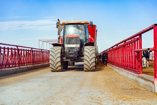 農場で運転している現代の赤い農業用トラクター