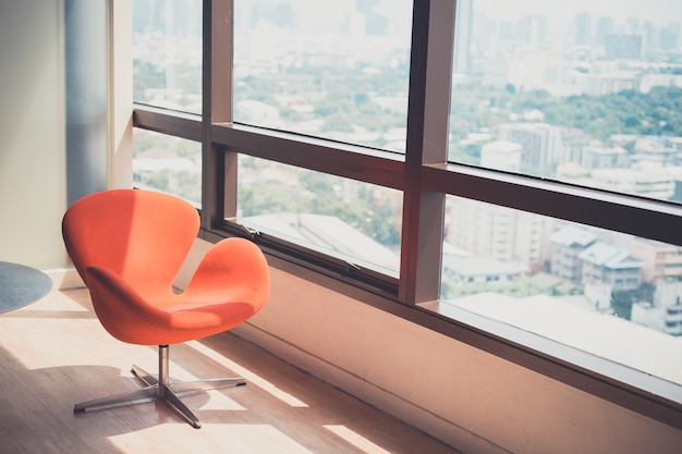 Modern red chair in room with panoramic cityscape