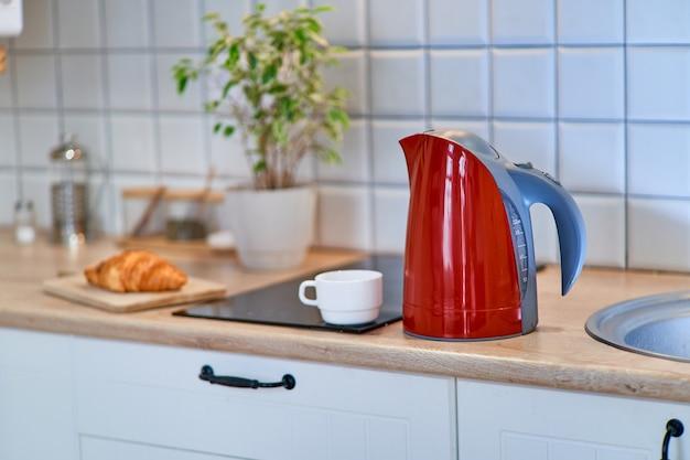 自宅のキッチンのテーブルにñ白いカップが付いたモダンな赤い電気ケトル