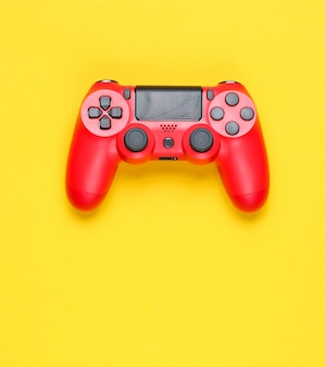 Modern red gamepad on a yellow background.