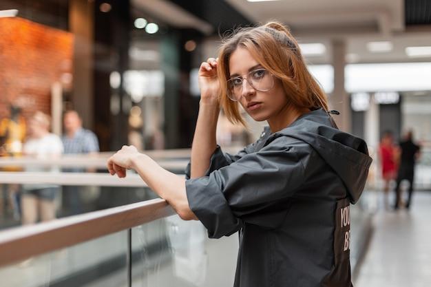 트렌디 한 안경에 세련된 후드 재킷에 현대 빨간 머리 젊은 여성이 밝은 유리 벽 근처의 상점에 서 있습니다. 유행 소녀는 쇼핑 센터에서 산책을 즐깁니다. 스타일.
