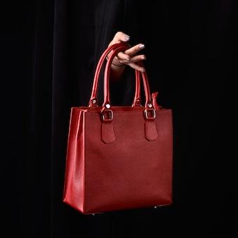 Современная красная кожаная сумка в женской руке.