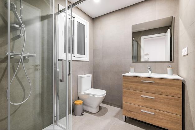 白いシンクと鏡付きのシャワーゾーントイレ木製ベース付きのモダンな改装されたバスルーム
