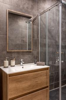 Современная отремонтированная ванная комната с душевой зоной на деревянном основании с белой раковиной и зеркалом. Premium Фотографии