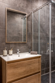 Modern refurbished bathroom with shower zone wooden base with white sink and mirror