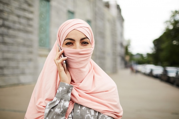 Modern religious woman talking on phone