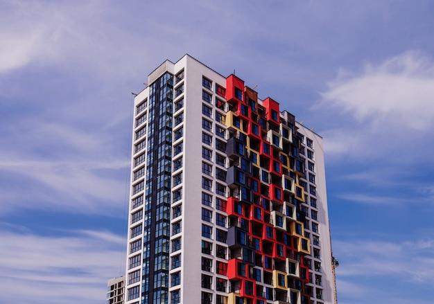 Современный жилой дом с ярким фасадом на фоне голубого неба. ипотека и строительство