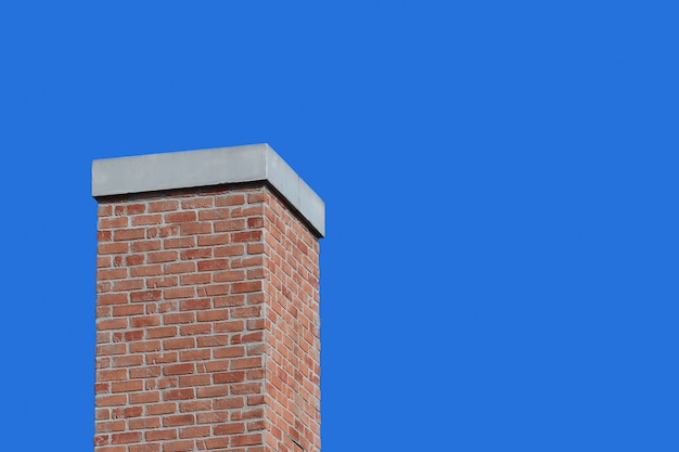 Modern retro brick chimney design with blue sky background.