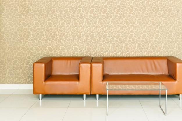 フロントロビースペースで待っているための豪華な金色の背景壁紙とモダンなレトロな茶色の革のソファ