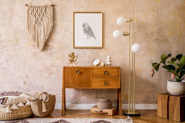 Modern retro composition of living room with wooden vintage commode, furniture, lamp, plant, carpet, pillows, macrame, gold mock up poster frame, plants, decoration and personal accessories.