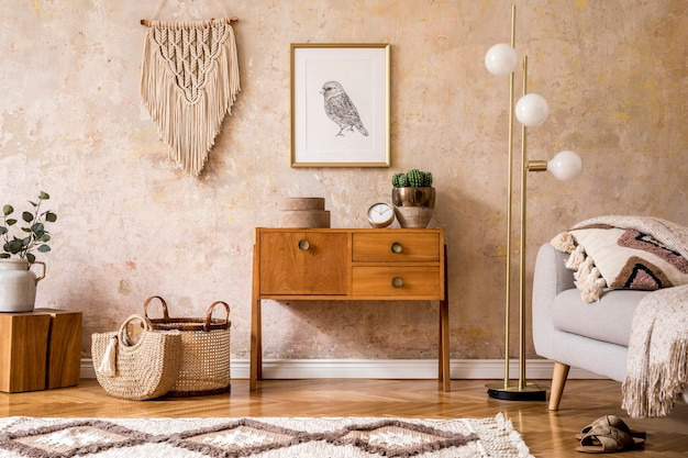 Modern retro composition of living room with wooden vintage commode, grey sofa, gold lamp, macrame, carpet, pillows, gold frame, plants, decoration and personal accessories.