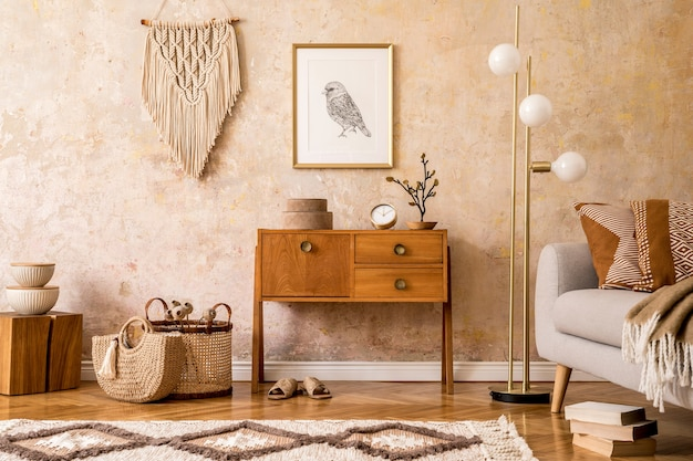 Modern retro composition of living room with wooden vintage commode, grey sofa, gold lamp, macrame, carpet, pillows, gold mock up poster frame, plants, decoration and personal accessories.