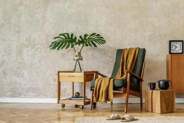 Современная ретро-композиция интерьера гостиной с дизайнерским креслом, кубом, чайником на подносе, тропическим листом, пледом, ковром, украшениями и элегантными личными аксессуарами в концепции ваби-саби.