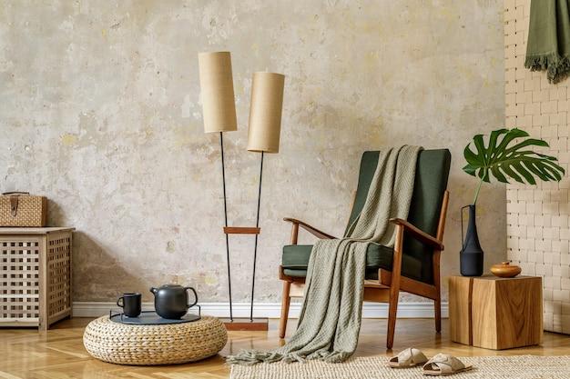Современная ретро-композиция интерьера гостиной с дизайнерским креслом, лампой, пуфом из ротанга, чайником на подносе, тропическими листьями, пледом, ковром и элегантными личными аксессуарами в концепции ваби-саби.