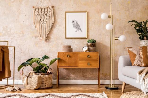 Современная ретро-композиция гостиной с деревянным винтажным комодом, серым диваном, золотой лампой, макраме, ковром, подушками, золотой рамкой, растениями, украшениями и личными аксессуарами.