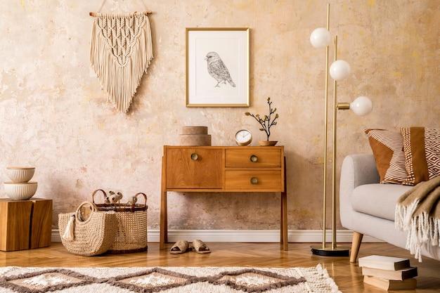 Современная ретро-композиция из гостиной с деревянным винтажным комодом, серым диваном, золотой лампой, макраме, ковром, подушками, золотой рамкой для плаката, растениями, украшениями и личными аксессуарами.