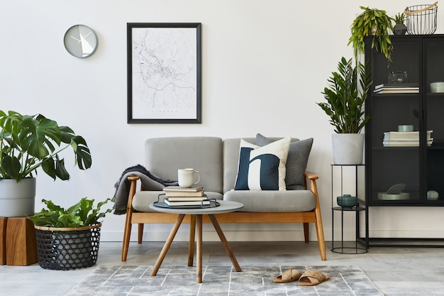 Современная ретро-концепция домашнего интерьера с дизайнерским серым диваном, журнальным столиком, растениями, мебелью, макетом карты плаката, украшениями и личными аксессуарами. стильный домашний декор гостиной.