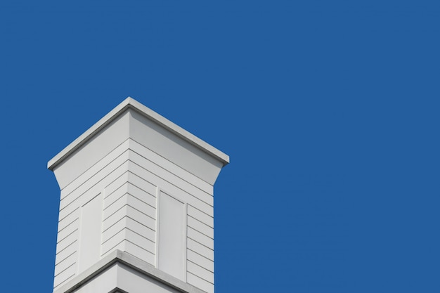 Modern retro white wood chimney with blue sky background.