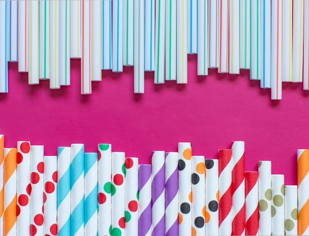 Современные многоразовые бумажные соломинки для питья как альтернатива пластиковым трубочкам для питья на розовых тонах