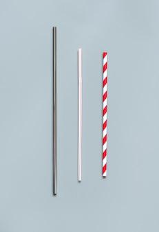 회색 배경 상위 뷰에 고전적인 일회용 플라스틱 마시는 빨대의 대체 대체품으로 현대 재사용 가능한 강철 및 종이 마시는 빨대