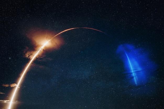 現代のロケットは衛星を軌道に打ち上げます。星空を爆風で飛ぶ宇宙船