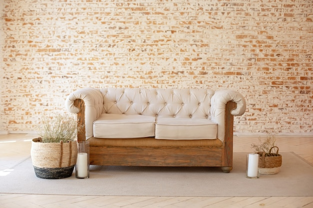 Modern rustic living room interior with white sofa and wicker baskets with dried flowers