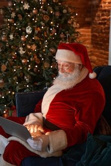 Modern santa claus with white beard sitting in armchair near beautiful christmas tree and using laptop