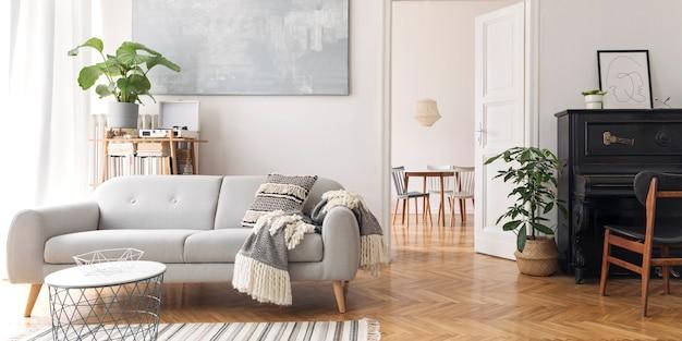 디자인 소파, 우아한 담요, 커피 테이블, 책꽂이, 식물 및 갈색 나무 마루가있는 현대 스칸디아 비아 거실 인테리어
