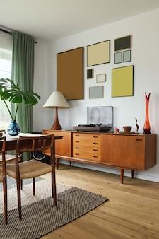 Современный скандинавский домашний интерьер гостиной с дизайнерской ретро-мебелью, тропической пальмой, стеной галереи, украшениями и элегантными личными аксессуарами в стильном домашнем декоре.