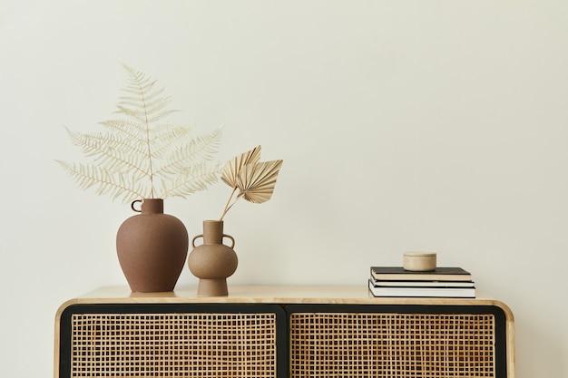 デザインの木製便器、セラミック花瓶の乾燥した葉、スタイリッシュな家の装飾の個人的なアクセサリーを備えたモダンなスカンジナビアの家のインテリア。レンプレート。スペースをコピーします。白い壁。