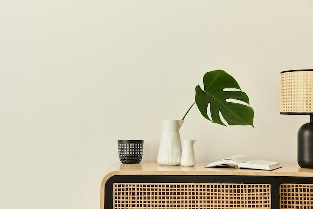デザインの木製の便器、花瓶の熱帯の葉、本やスタイリッシュな家の装飾の個人的なアクセサリーを備えたモダンなスカンジナビアの家のインテリア。レンプレート。スペースをコピーします。白い壁。
