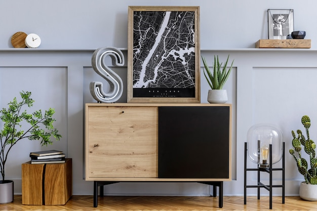 Modern scandinavian home interior with frames, design wooden commode, big cement letter, cacti, plants, decoration, shelf and personal accessories in stylish home decor.