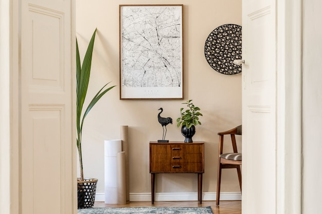 Современный скандинавский интерьер гостиной с коричневой рамкой для плаката, дизайнерским ретро-комодом, стулом, декором из ротанга, ковром, растениями и элегантными аксессуарами. . стильная домашняя постановка. джапанди.