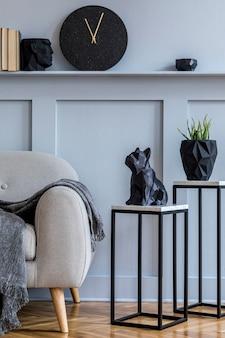 Современный скандинавский интерьер гостиной с серым диваном, пледом, мраморными стульями, растениями, свечой, часами, книгами и элегантными личными аксессуарами в стильном домашнем декоре.