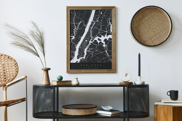 포스터 프레임, 디자인 캐비닛, 꽃병 잎, 등나무 안락 의자, 책 및 세련된 가정 장식의 우아한 액세서리가있는 현대 스칸디나비아 거실 인테리어