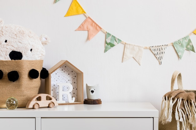The modern scandinavian newborn baby room with copy space, wooden car, plush toys and clouds. hanging cotton flags and white stars. minimalistic and cozy interior with white walls.
