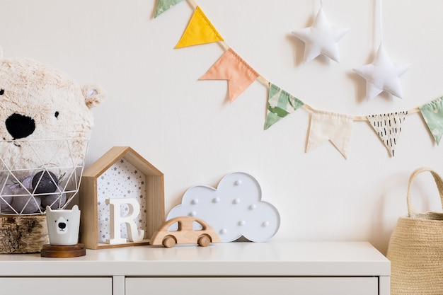 The modern scandinavian newborn baby room with copy space, wooden car, plush toys and clouds