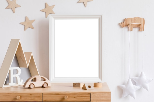 The modern scandinavian newborn baby room with frame, wooden car, plush toys, children accessories, clouds and hanging garland. minimalistic and cozy interior with white walls.