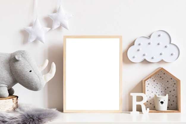 The modern scandinavian newborn baby room with mock up photo frame, wooden car, plush toys and clouds. hanging cotton flags and white stars. minimalistic and cozy interior with white walls.