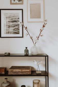 Современная скандинавская гостиная с красивыми деталями, такими как черные полки, вазы, рамы, деревянные шкатулки, хлопок.