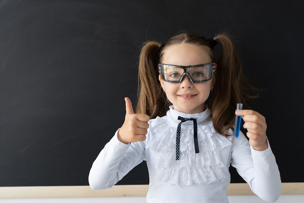 A modern schoolgirl at the blackboard conducts experience