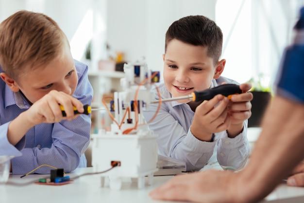 Современная наука. позитивно довольные мальчики строят робота во время урока естествознания