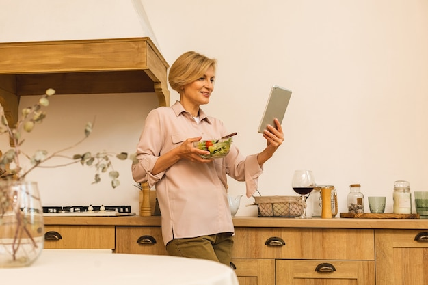 Modern senior aged mature woman eating fresh green salad and vegetables in kitchen, smiling happy. helthy lifestyle concept. using tablet.