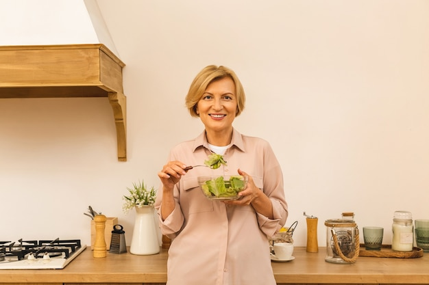 Modern senior aged mature woman eating fresh green salad and vegetables in kitchen, smiling happy. helthy lifestyle concept.