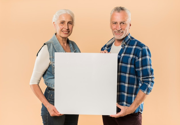 Modern senior couple holding board template