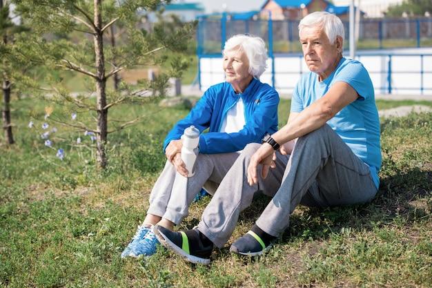 芝生で休んで現代の年配のカップル