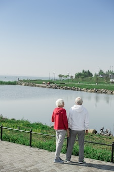 Modern senior couple standing by lake