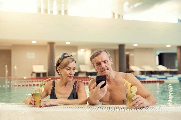 スイミングプールでスマートフォンを使用して現代の年配のカップル