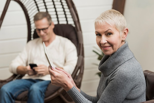 Modern senior couple using wireless devices