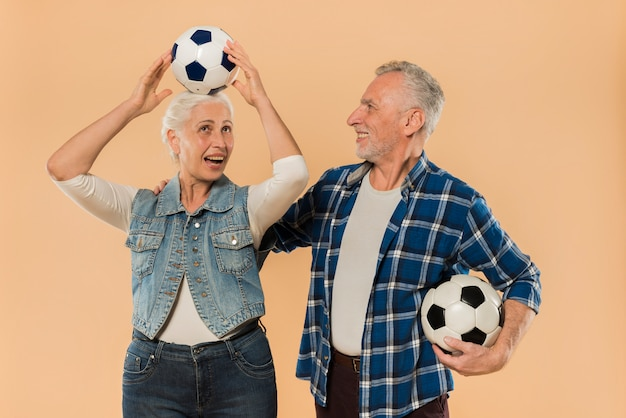 Modern senior couple with football